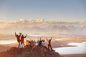 Large group of happy friends is having fun on mountain top and looks at mountain's valley. Adventure or travel concept