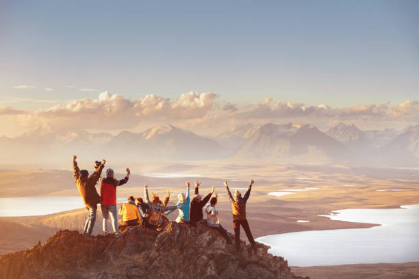 Large group of happy friends in mountains area Large group of happy friends is having fun on mountain top and looks at mountain's valley. Adventure or travel concept travel stock pictures, royalty-free photos & images