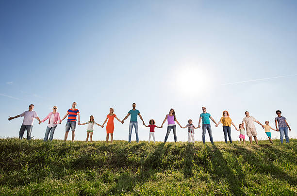 Large group of happy people holding hands against the sky. Low angle view of group of smiling people standing in a meadow against the sky and holding hands while looking at camera. Copy space. people in a row stock pictures, royalty-free photos & images
