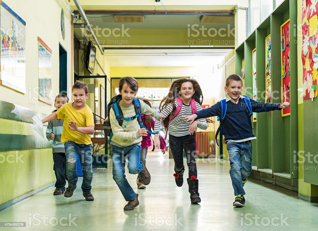 Large group of happy school children running in the hall. stock photo