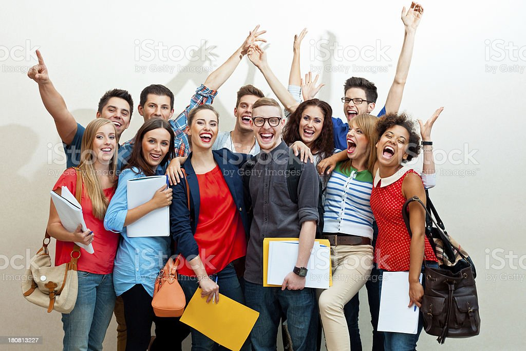 Large group of happy students Large group of diverse high school students standing against white wall, embracing, raising hands and laughing at camera.  20-24 Years Stock Photo