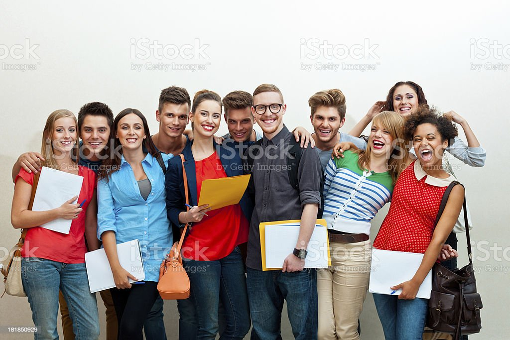 Large group of happy students Large group of diverse of college students standing against white wall, embracing and laughing at camera.  20-24 Years Stock Photo