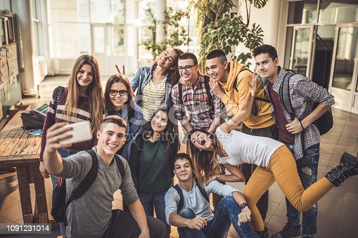 Large group of happy high school students having fun while taking a selfie with mobile phone in a hallway.