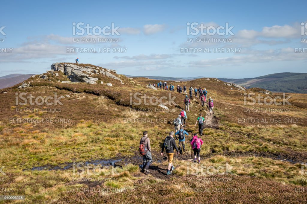 Large group of hikers walking into distance at the Wicklow Mountains, Ireland, on a sunny day stock photo