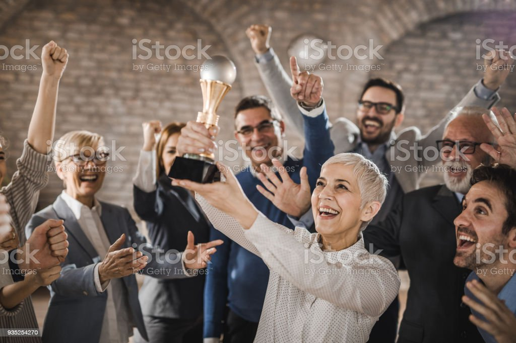 Large group of joyful business colleagues celebrating their success by winning a trophy in the office. stock photo
