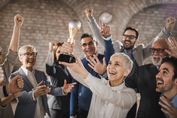 large group of joyful business colleagues celebrating their success by winning a trophy in the office. - trophy award stock photos and pictures