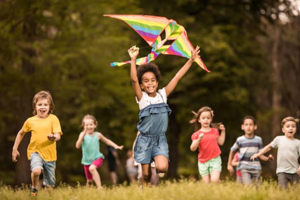 İlkbaharda uçurtma ile çalışan neşeli çocuklar büyük bir grup. stok fotoğrafı