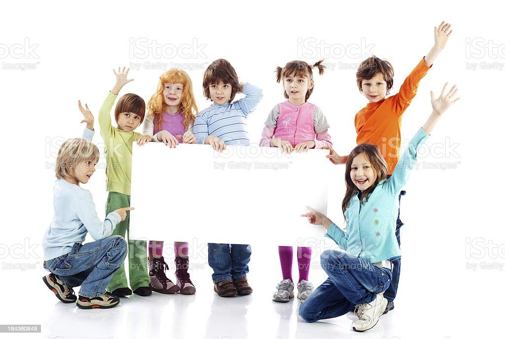 Grande grupo de crianças segurando um grande papel em branco. - foto de acervo