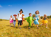 istock Large group of kids in Halloween costumes run 513234365