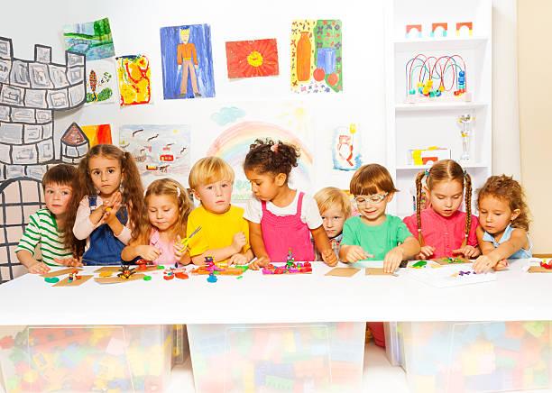 große gruppe von kindern spielen mit plasticine in class - knete spiele stock-fotos und bilder