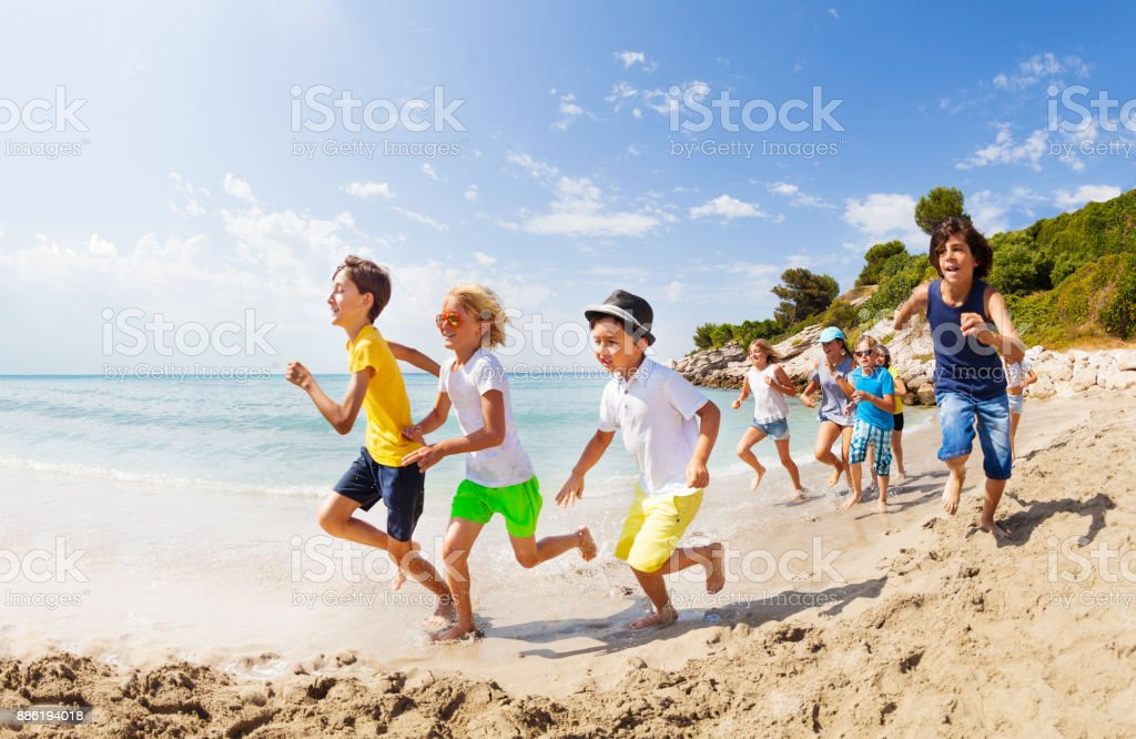 Large group of kids run on a beach along the sea stock photo