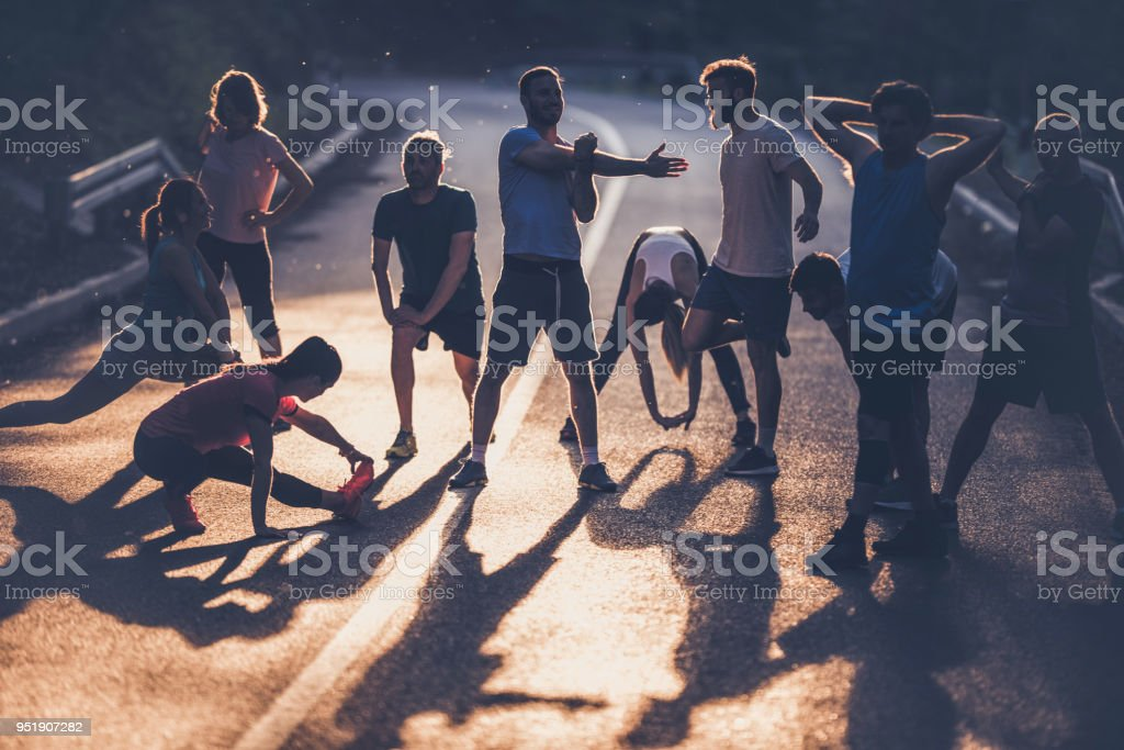 Large group of marathon runners warming up on a road at sunset. stock photo