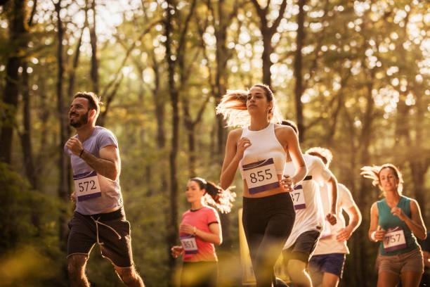 gran grupo de corredores motivados correr un maratón en la naturaleza. - maratón fotografías e imágenes de stock