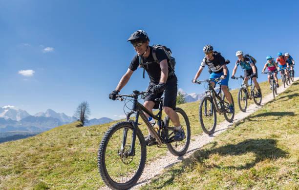 Große Gruppe von Mountainbikern Abfahrt vor Mt. Marmolada, Italien – Foto