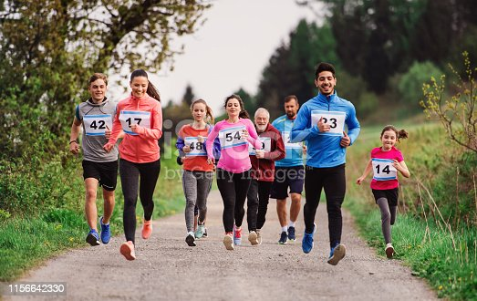 A large group of active multi generation people running a race competition in nature.