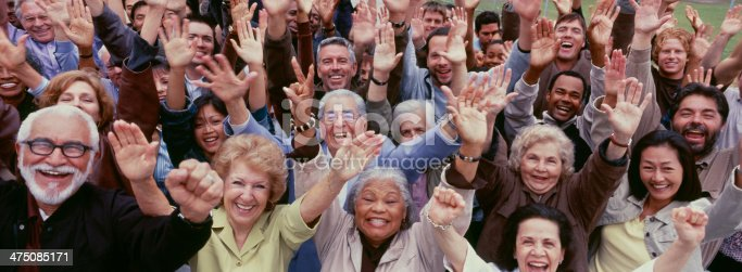 istock Large group of multi-ethnic people cheering with arms raised 475085171