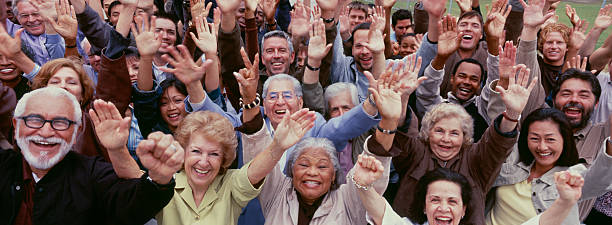 Large group of multi-ethnic people cheering with arms raised Large group of multi-ethnic people cheering with arms raised 65 69 years stock pictures, royalty-free photos & images