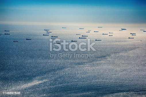 Silhouettes of multiple oil tankers off the coast of Texas in the Gulf of Mexico near Galveston Bay approaching an American refinery in Texas City, Texas located south of Houston near the city of Galveston.