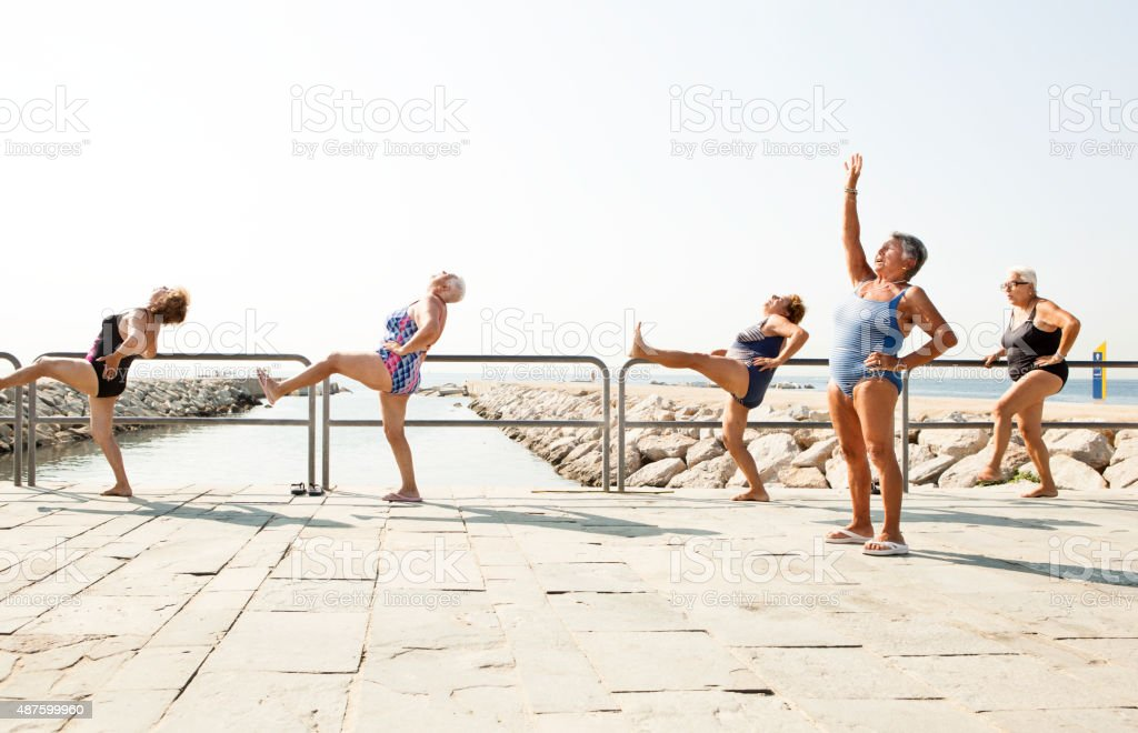 Large group of old people having an exercise class stock photo