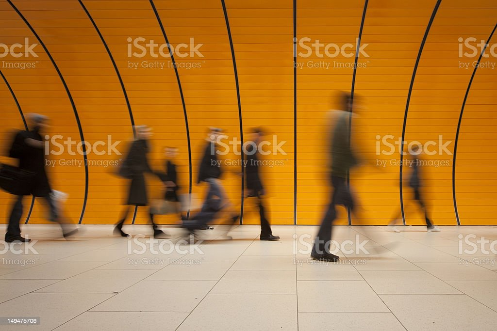 large group of people against modern orange subway tube stock photo