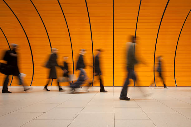 large group of people against modern orange subway tube XXXL - motion blurred commuters in different sizes against modern orange subway walkway, orange wall in background - tiled floor in foreground - camera canon 5D mark II - unsharped RAW - adobe colorspace subway platform stock pictures, royalty-free photos & images