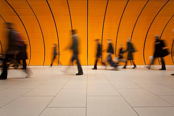large group of people against modern orange subway tube  subway platform stock pictures, royalty-free photos & images