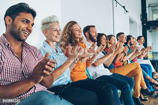 858148040 istock photo Large group of people applauding 840894220