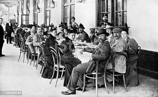 Large group of men and women sitting at tables at a train station in Saint Petersburg, Russia. The Russian Empire era (circa 19th century). Vintage halftone photo etching circa late 19th century.