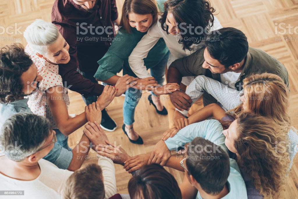 Large group of people connecting hands in a circle