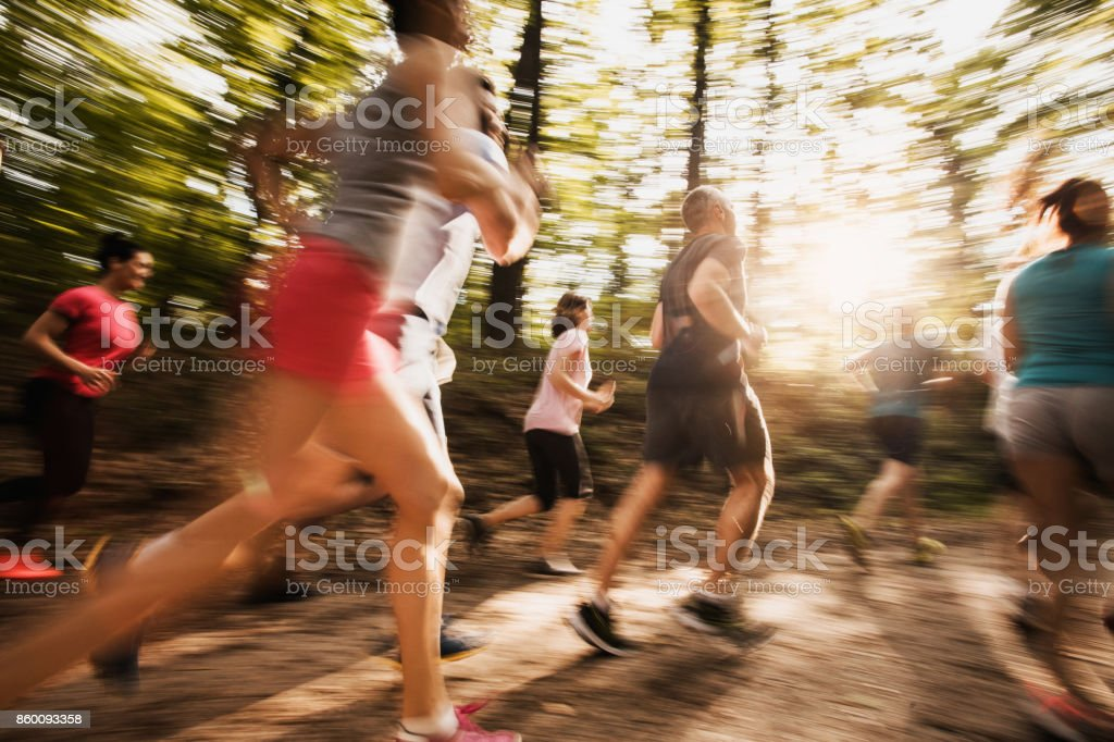 Large group of people in blurred motion running a marathon in nature. stock photo