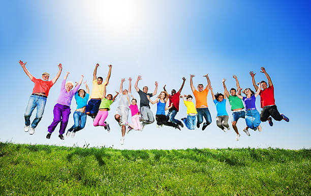 large group of people jumping against the clear sky. - african youth jumping for joy stock photos and pictures