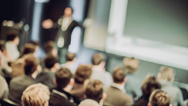 large group of people listening to a presentation - soft focus stock photos and pictures