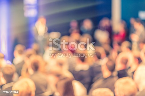 526272636istockphoto Large Group of People Listening to a Presentation 526272944