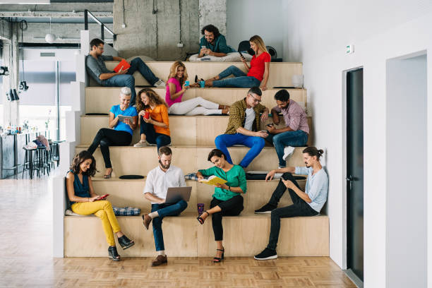 large group of people networking in a loft office - sitting laptop стоковые фото и изображения