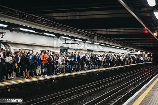 London, UK - June 6, 2019: Large group of people on a platform of Moorgate station of London Undeground, trains delayed. London Underground is the oldest underground railway in the world.