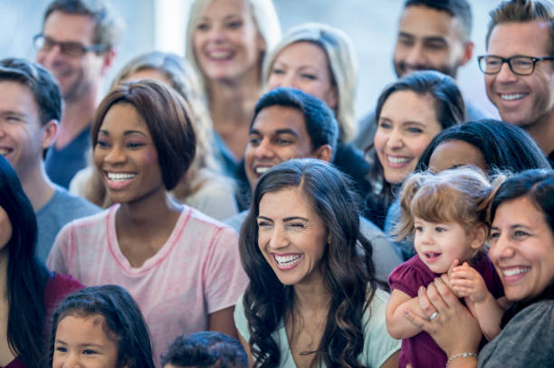 Large Group Of People A large, diverse group of people are doing a photo shoot indoors. They are facing to the left of the camera, and smiling together. One woman is holding her child in her arms, global village stock pictures, royalty-free photos & images