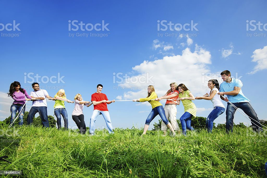 Group of young people divided into two teams and playing by pulling...