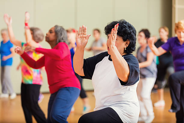 Large group of people take dance lessons A large group of people learn to Zumba or line dance at senior center. The active seniors clap and dance as they enjoy dancing. The group consists of men and women. community center stock pictures, royalty-free photos & images