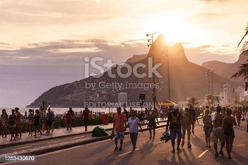 Large group of people walking on Ipanema Beach boulevard at sunset in Rio de Janeiro, Brazil.