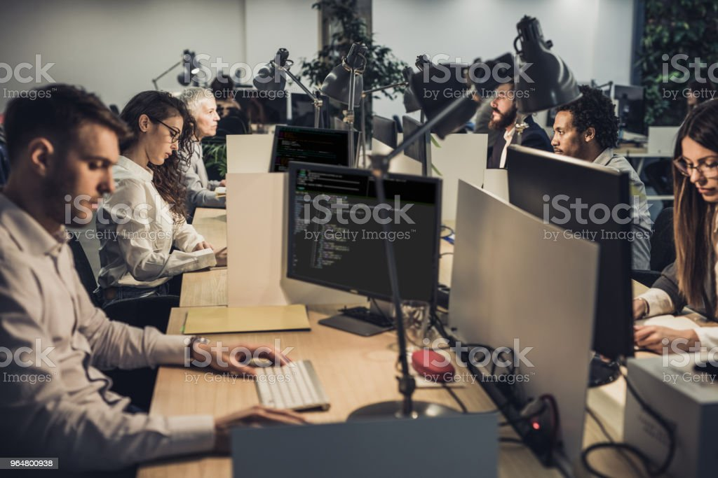 Large group of computer programmers working on desktop PC's in the office. Large group of programmers coding programs on desktop PC's at corporate office. Adult Stock Photo
