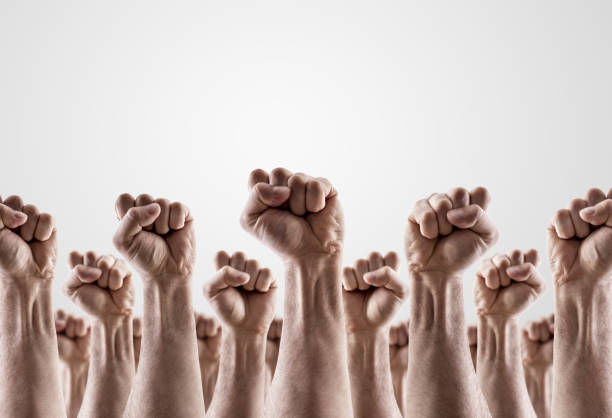 Large group of raised hands showing fists stock photo