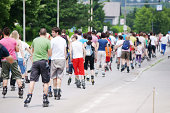 Celje, Slovenia - June 5, 2011: Large group of roller skaters of all ages on the street. Event is organized within Recreation and Sports week 2011 in Celje. There were around 170 skaters present. Green foliage in background.