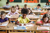istock Large group of school kids writing a test on a class in the classroom. 1038332258