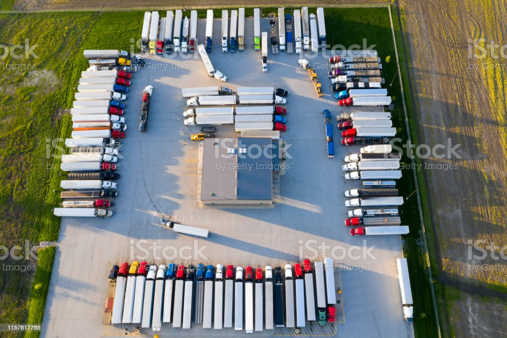 Aerial view of a large group of semi trucks parked at a highway truck...