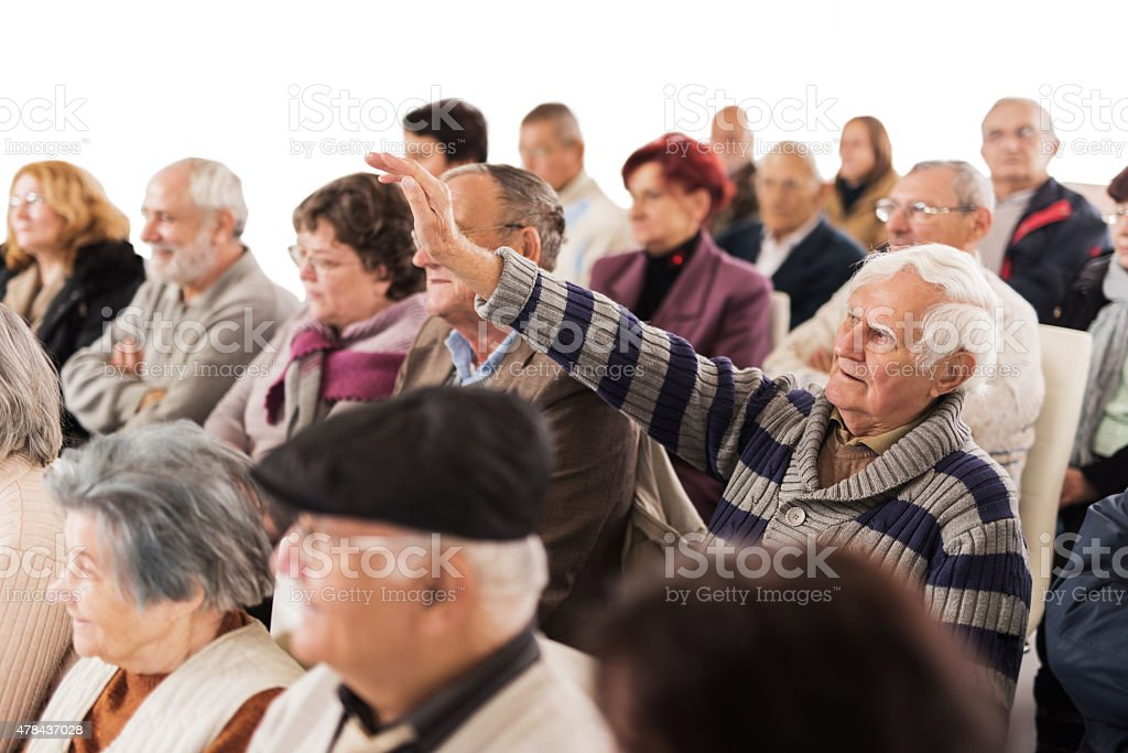 Large group of senior people attending a seminar. stock photo