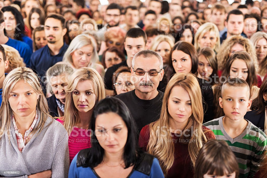 Large group of serious people standing together. stock photo