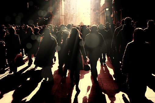 Large group of silhouetted people walking on busy street