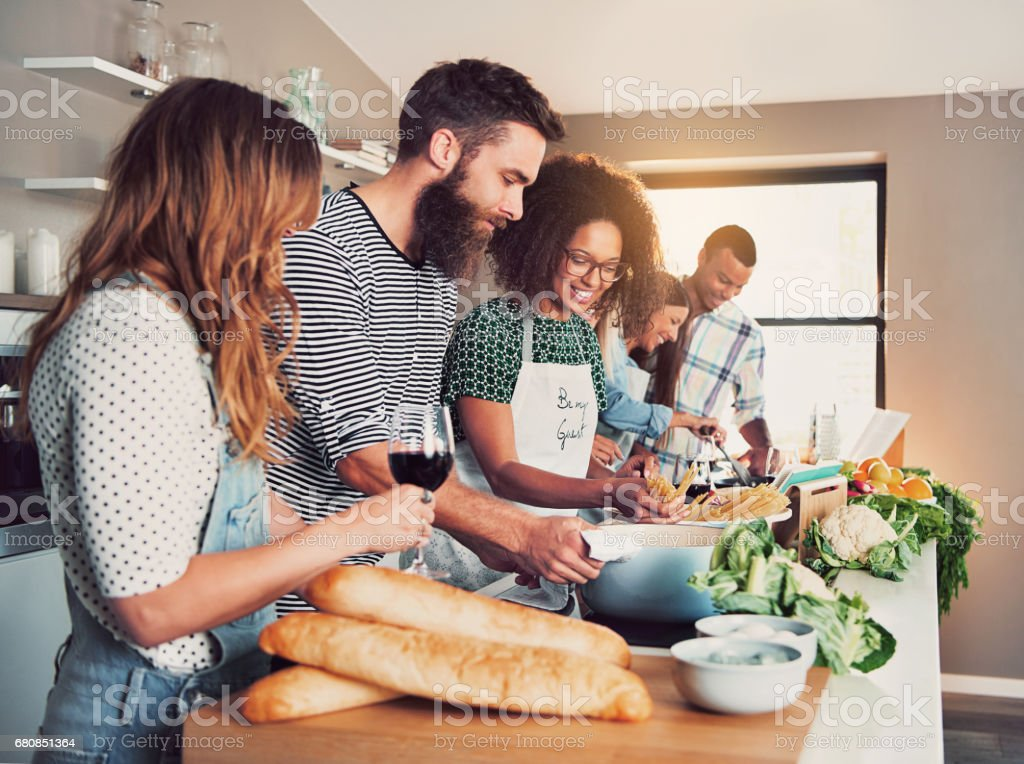 Large group of six friends cooking at table stock photo
