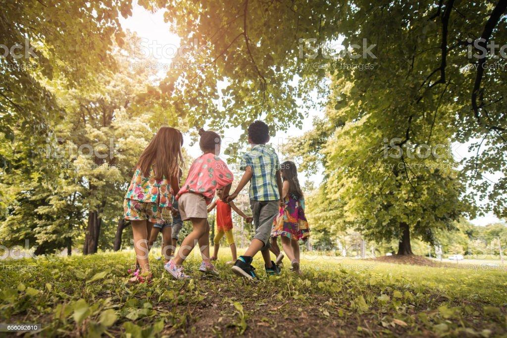 Grand groupe de petits amis à jouer anneau-autour-les-roses dans le parc. - Photo