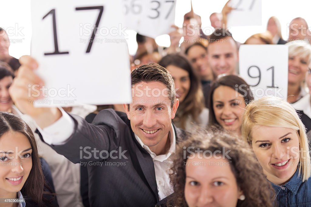 Large group of smiling business people at auction. stock photo